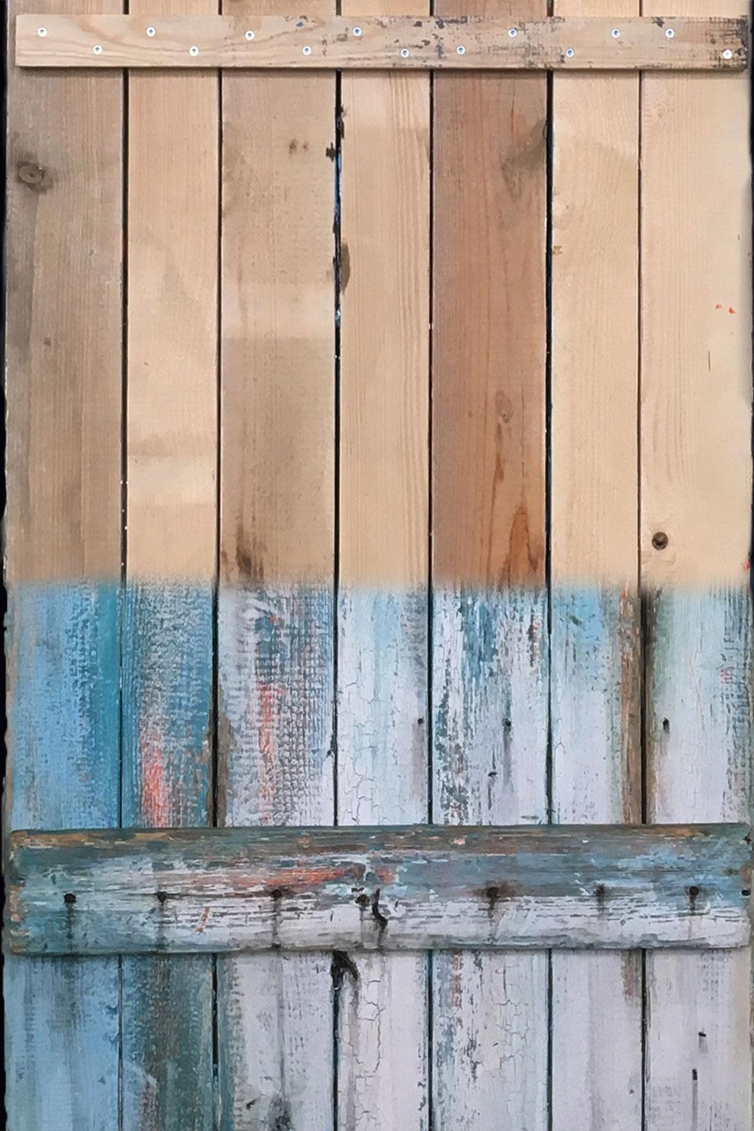 Holzbalken in der Bearbeitung: Unten hellblau gestrichene, verblichene Farbe und angegriffenes Holz, oben unbehandelt