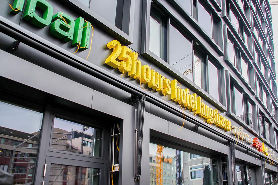 Fassade mit Buchstaben gelb und gruen vor der Montage der Neonroehren, mit heraushaengenden Kabeln