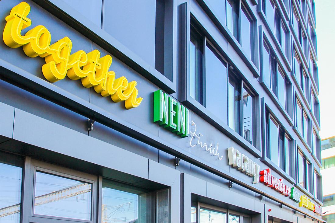 Geschwungener Schriftzug für das Logo von together mit gelben Neonbuchstaben, die auch bei Tageslicht auffallen
