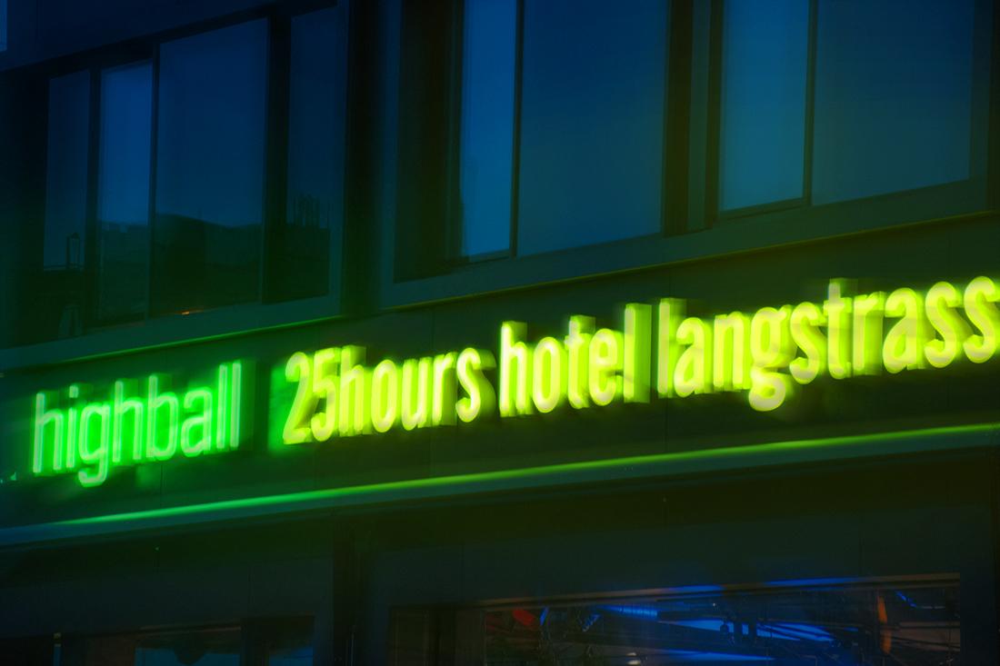 Nachtaufnahme: Neon-Schriftzuege an der Fassade des Hotels strahlen gelb und gruen im Dunkeln