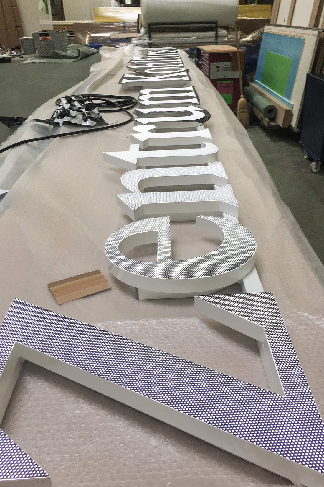 Leuchtschrift liegt fertig beklebt auf dem Arbeitstisch und ist bereit zur Montage.