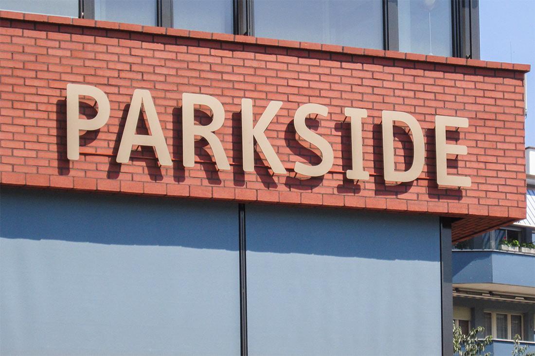 Leuchterbung Parkside mit Fassadenbeschriftung: Einzelne hinterleuchtete Buchstaben auf roher Backsteinwand montiert.