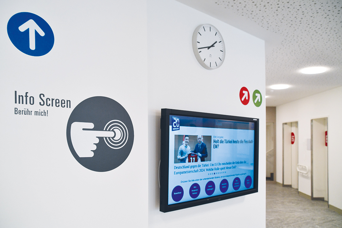 Signaletik Alters- Pflegeheim: Infowand mit Display, Uhr, Info Screen und Pfeilen