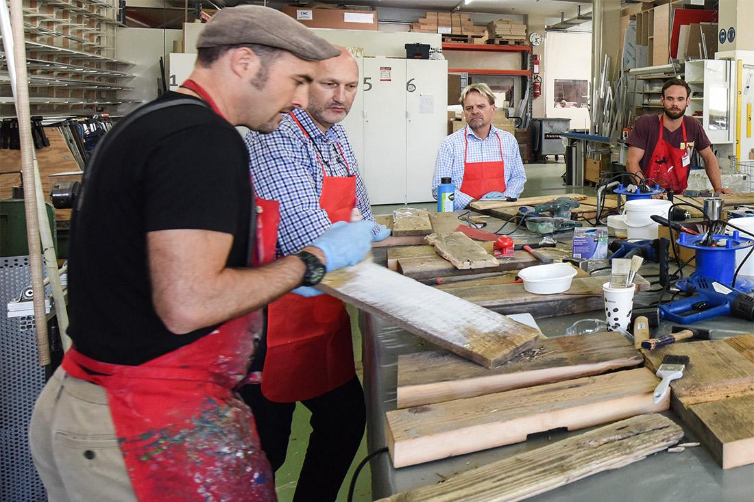 Ein Mitarbeiter bestreicht eine Holzlatte