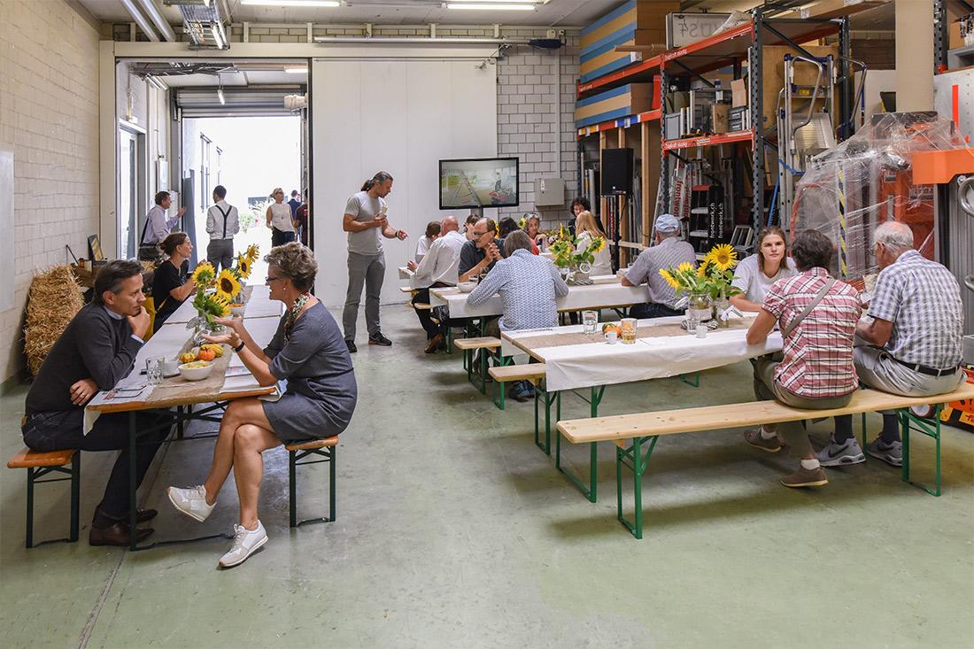 Besucher sitzen auf geschmückten Festbänken und diskutieren