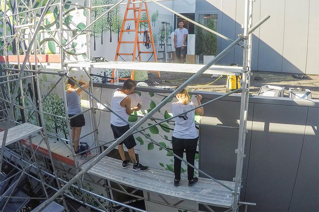 Drei Arbeiter verkleben Folie auf Gerüst drei geschossig vor Fassade