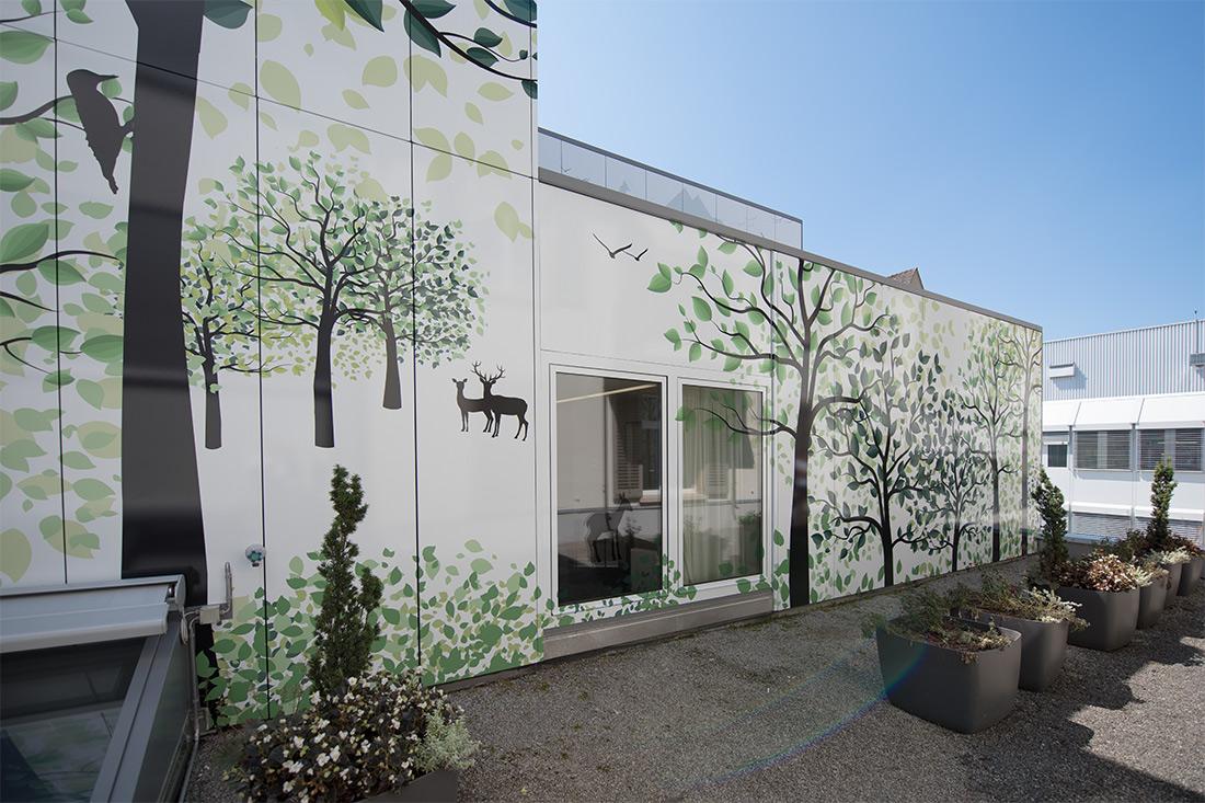Ansicht von unten links an fertig beklebte Fassade (Sujet der Folie: Wald mit Bäumen, Specht, Reh und Hirsch)