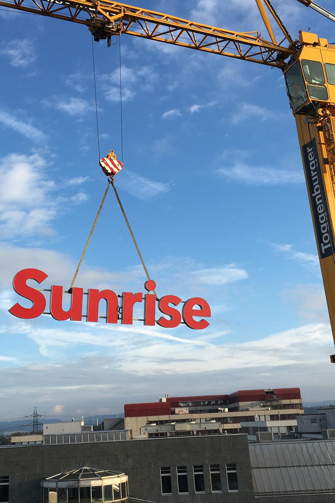 Schwebende Sunrise Leuchtbuchstaben werden in Position gebracht