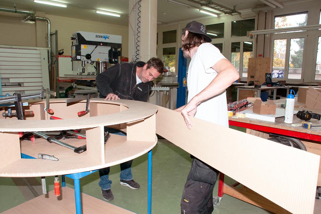 Arbeiter bauen aus Holz ein rundes Podest