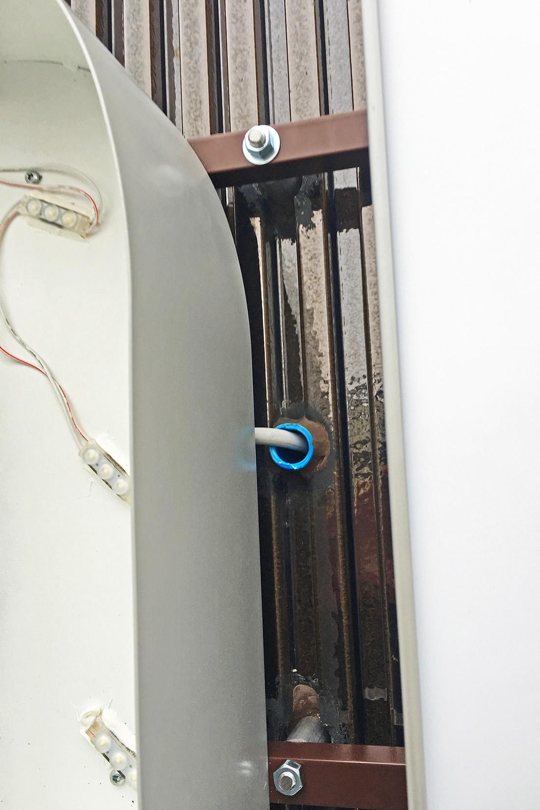 Detailansicht der LED-Leuchtschrift mit Stromanschluss aus der Wand.