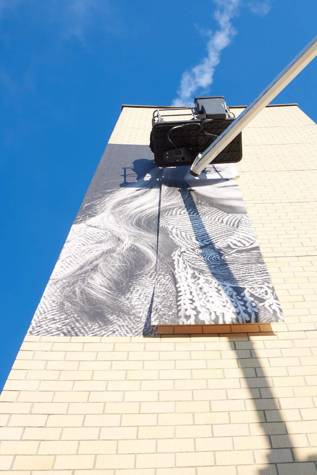 Ausgefahrene Hebebühne vor Backstein-Fassade, Xxl Bild wird in Bahnen an Mauer geklebt