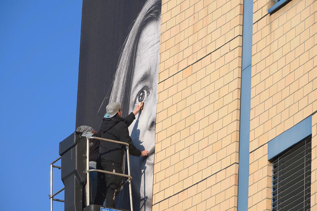 Arbeiter auf Skyworker kleben Folie an eine Backsteinwand