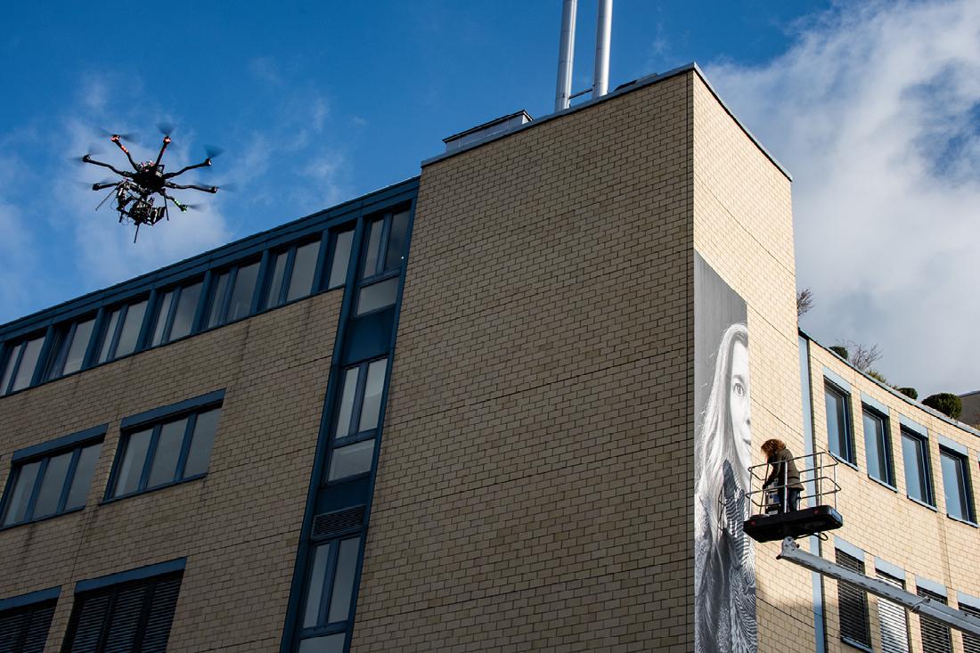 Drohne in der Luft filmt Sandra Schmid beim arbeiten auf der Hebebühne an der Wand