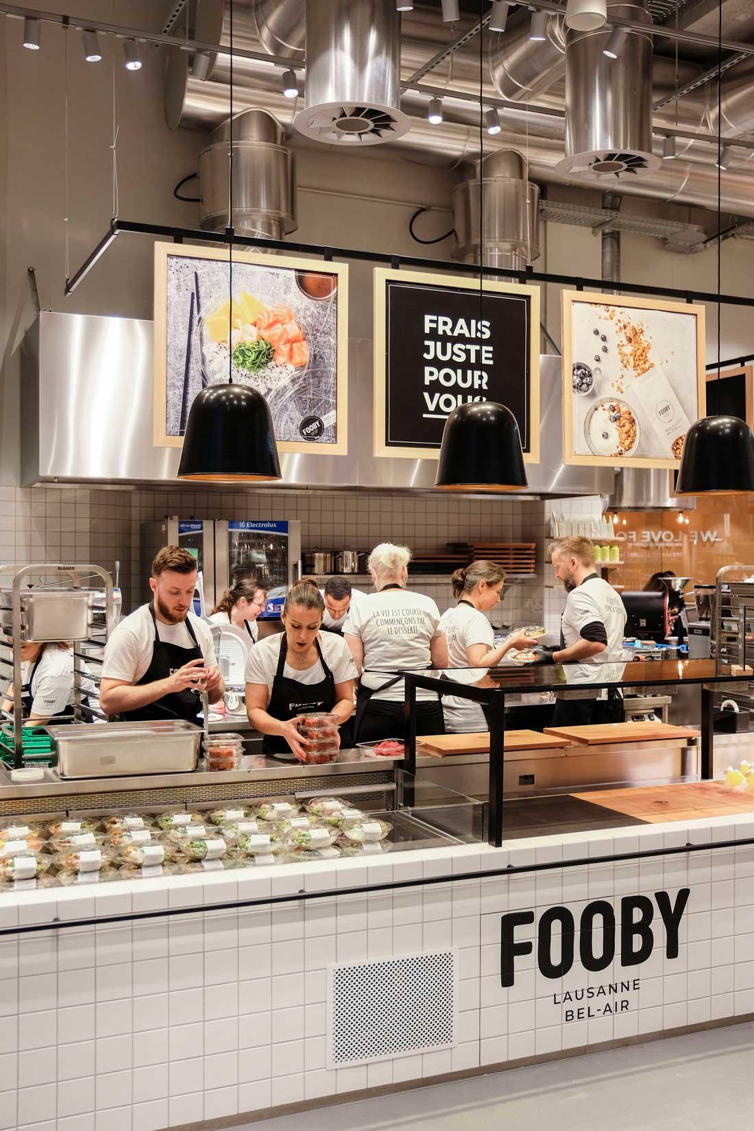 Ladenbau Coop Fooby-Store: Theke hell gross und uebersichtlich, mit Mirarbeitenden